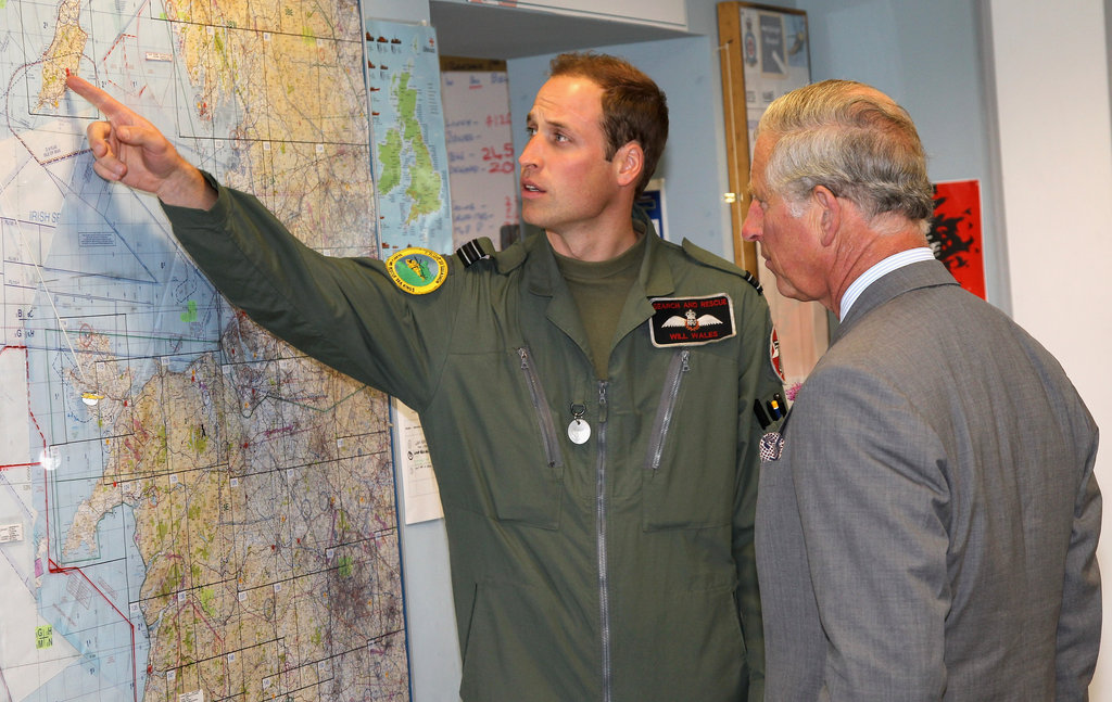 Prince William pointed out something on a map to his father Prince Charles.