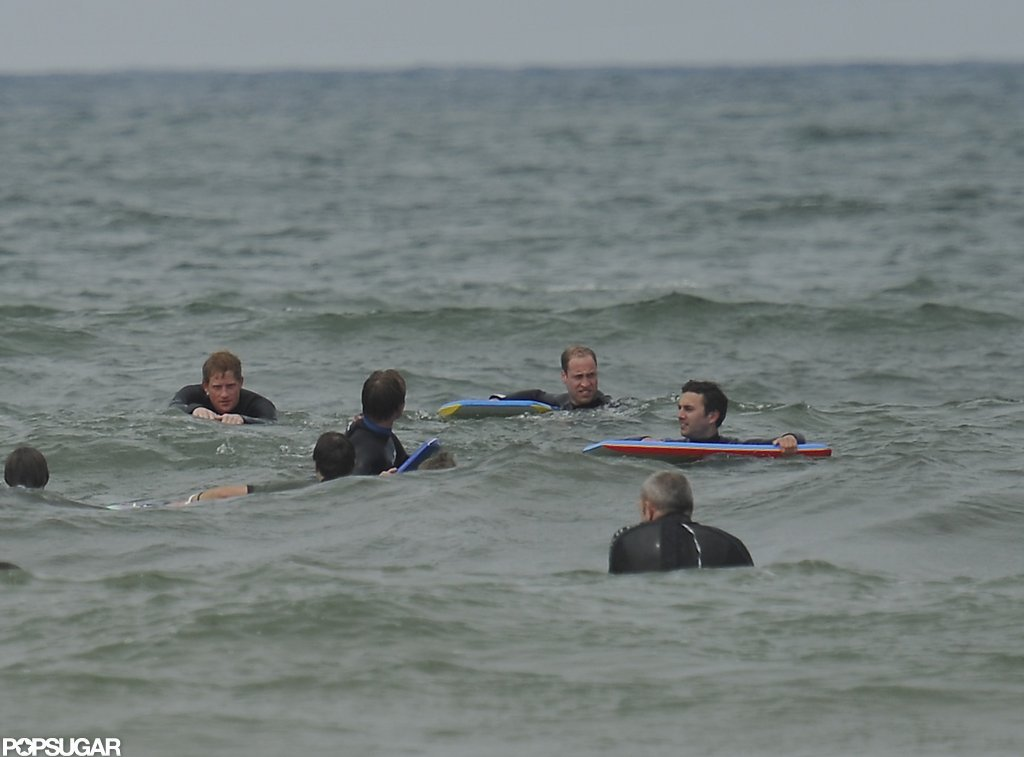 Prince William and Prince Harry hug out with fellow beach-goers in the ocean over the weekend.