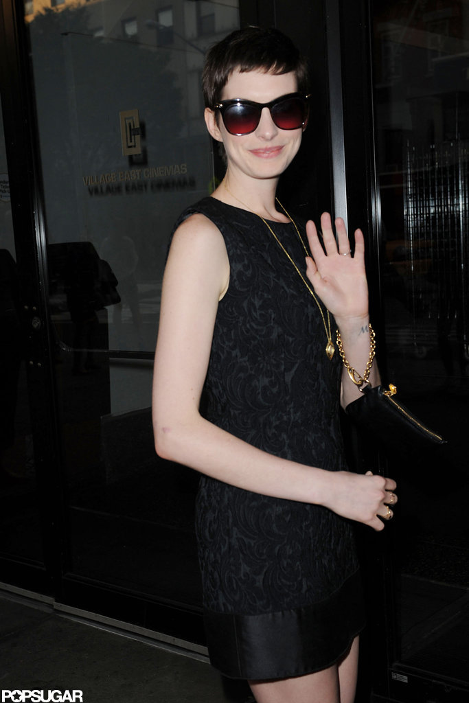 Anne Hathaway waved as she walked into the Shut Up & Play the Hits screening in NYC.