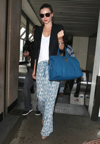 If only our airport looks were half this chic — Miranda capitalized on the pajama-pant trend in a pair of breezy, printed trousers, which she balanced with more polished pieces up top.