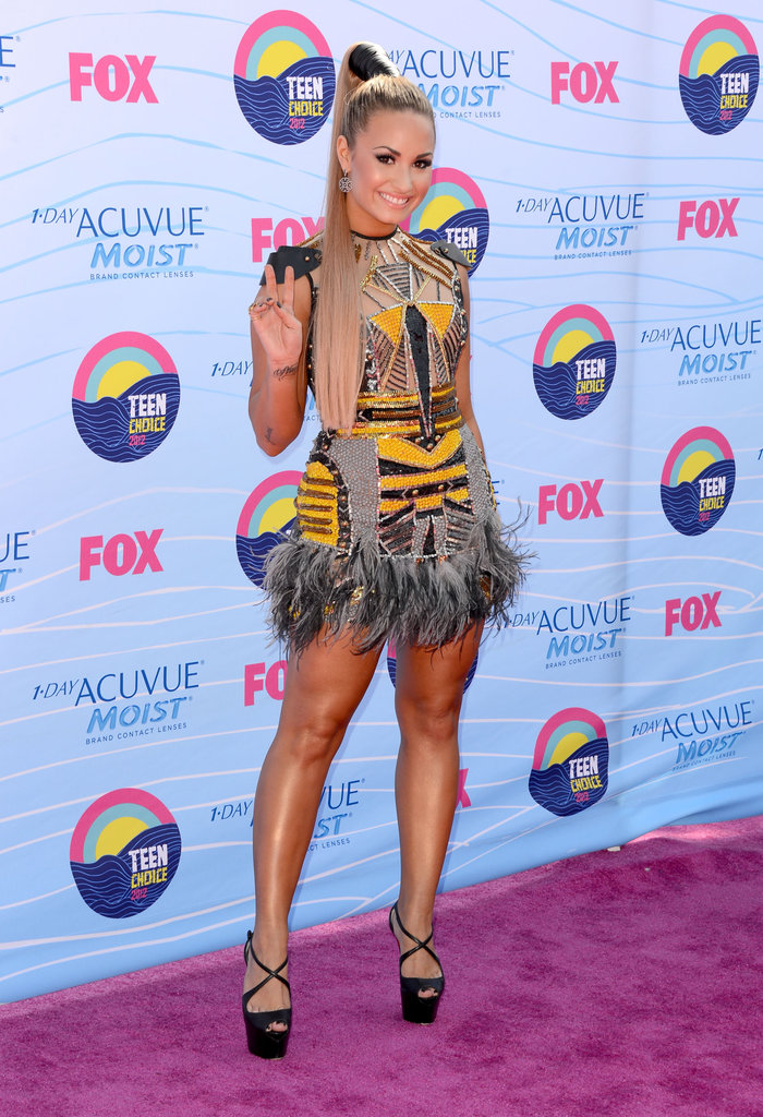 Demi Lovato made a statement in a yellow and gray Falguni & Shane Peacock mini dress, Christian Louboutin platform sandals and a dramatic pony tail.
