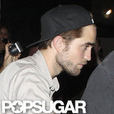 Robert Pattinson wore a backwards baseball cap.