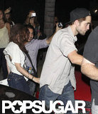 Robert Pattinson held onto Kristen Stewart amidst paparazzi.