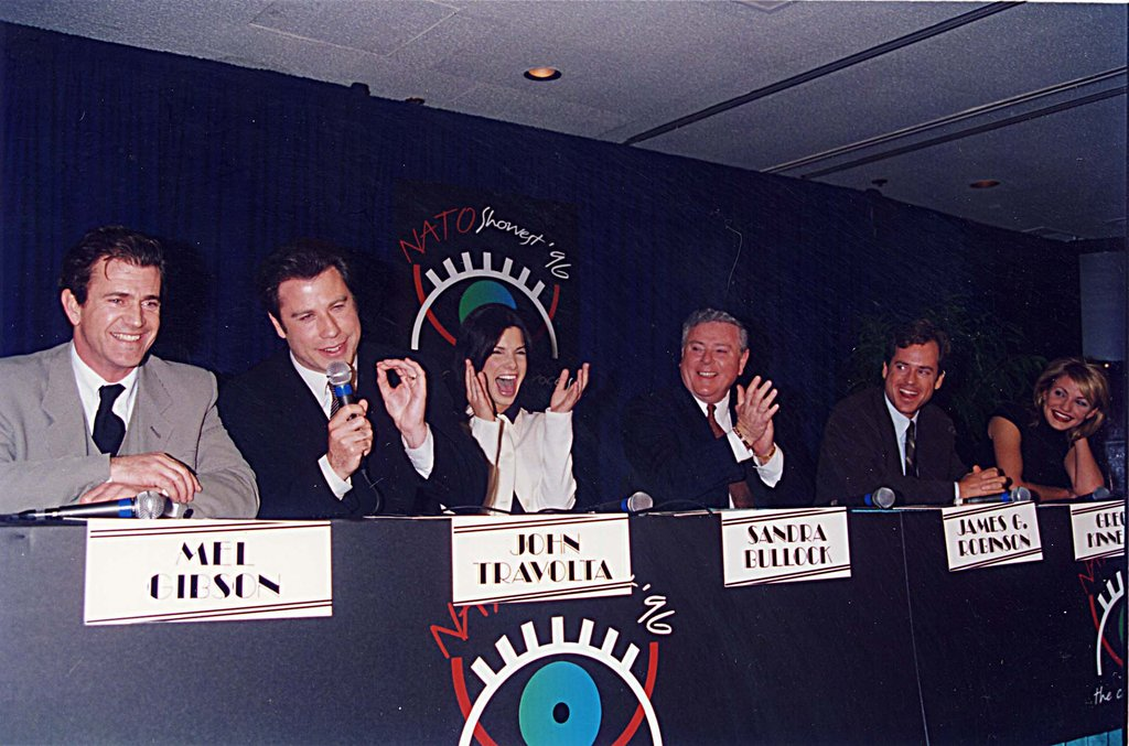 Sandra Bullock sat on a September 1996 ShoWest panel with fellow actors Mel Gibson, John Travolta, Greg Kinnear, Cameron Diaz, and James Robinson.
