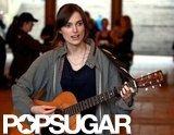 Keira Knightley strums a guitar on set.