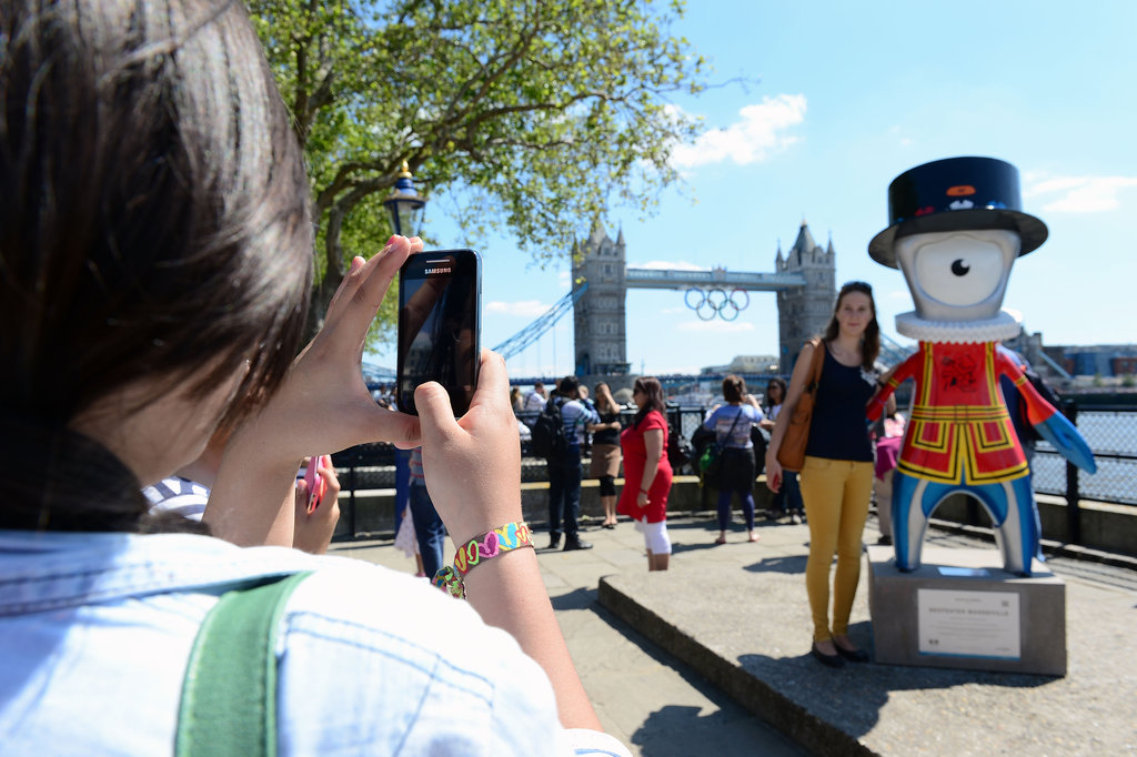 Tourists took pictures beside the Olympic mascot in front of the Tower Bridge.