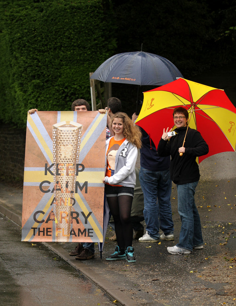 "Locals held a sign that read ""Keep Calm and Carry the Flame"" during the torch relay in Tillington, England."