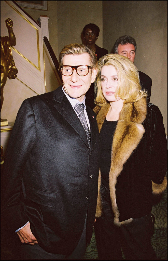 Longtime friend Catherine Deneuve shared a moment with him at the opening of his eponymous foundation in March 2004.