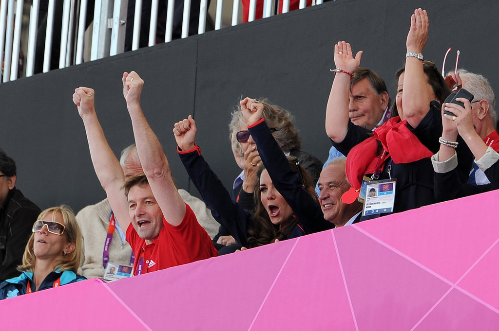 Kate Middleton cheered with her arms in the air.