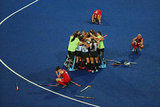 Disappointed GB teammates slumped down as Argentina's hockey team celebrated their win.
