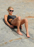 Paris Hilton adjusted her black swimsuit.