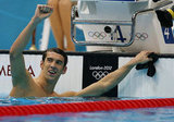 Michael Phelps put his arm in the air after winning gold in the men's 100m butterfly final.