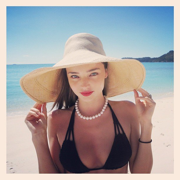 Miranda Kerr stayed shaded under a sun hat on the beach. Source: Instagram user mirandakerrverified