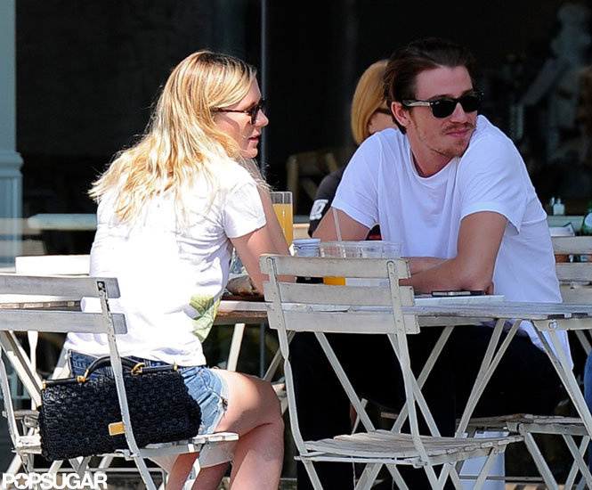 Kirsten Dunst propped her Dolce & Gabbana bag on her chair as she brunched with Garrett Hedlund.