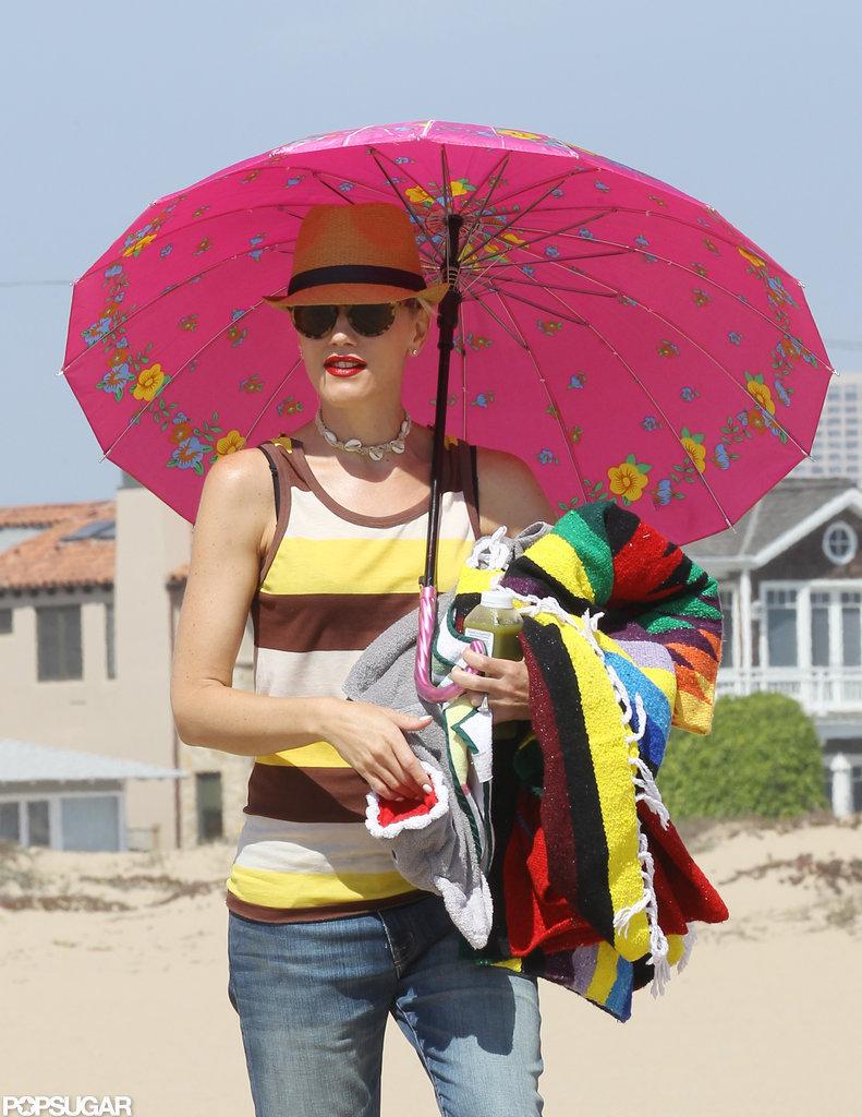 Gwen Stefani carried a bright pink umbrella at the beach.