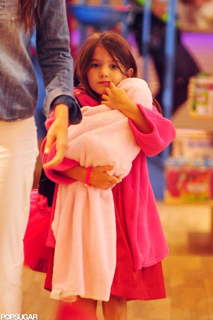 Suri Cruise wore a bright pink jacket and held her baby-doll in a pink blanket.