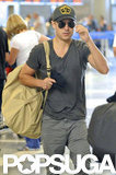 Zac Efron sported a gray v-neck t-shirt and a Military hat at LAX Airport.