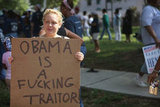 A woman held a sign in protest of Obama.