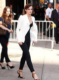Emma Watson wore a white blazer over black pants.