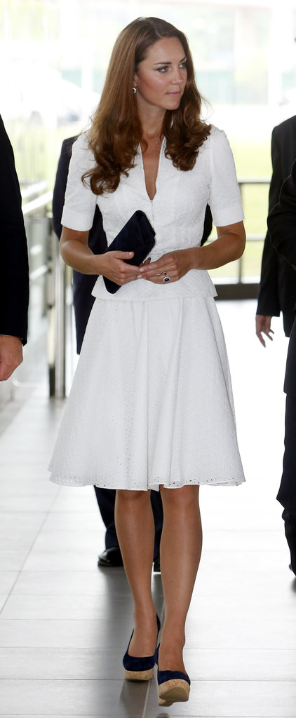 Midday, the brunette beauty stunned in a crisp white Alexander McQueen skirtsuit and navy blue Stuart Weitzman wedges. This isn't the first time Kate has worn a McQueen skirt-suit — she actually wore an ivory-hued version for the kickoff of Diamond Jubilee celebrations earlier this year.