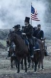 Daniel Day-Lewis, as Abraham Lincoln, leads troops on the battlefield.