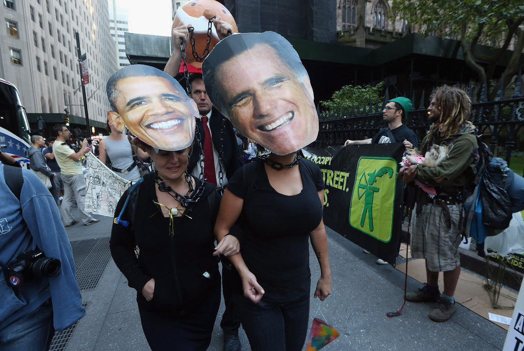 Two women protesting with Occupy in New York City wore Barack Obama and Mitt Romney masks.