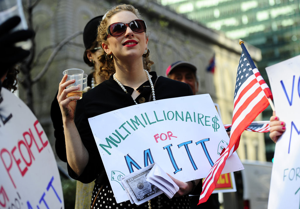 """This woman held a sign against presidential candidate Mitt Romney stating """"Multimillionaires for Mitt"""" outside his campaign fundraiser in New York."""