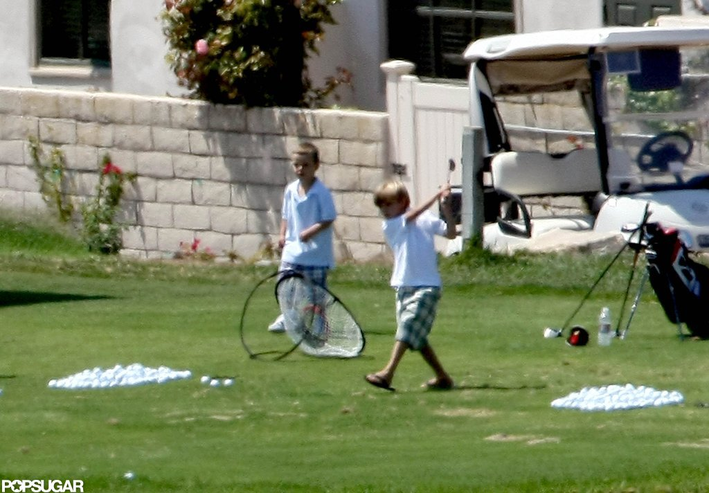 Romeo and Cruz Beckham played around with their clubs in LA in August 2009.