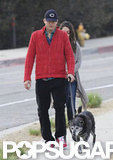 Ashton Kutcher wore a red jacket and cap to walk his dog in LA.