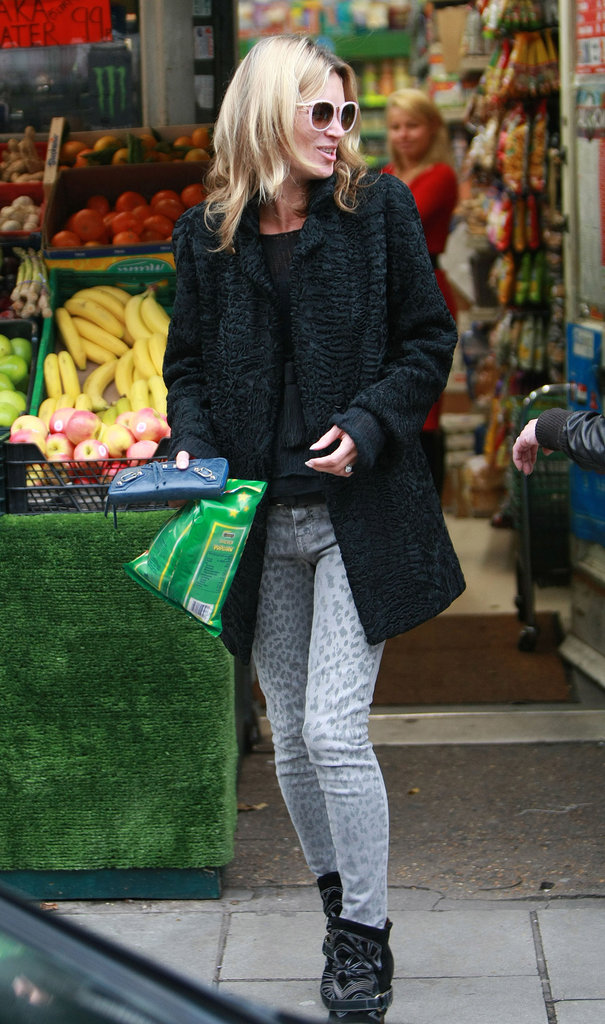 Kate Moss wore printed skinny jeans and a black coat.