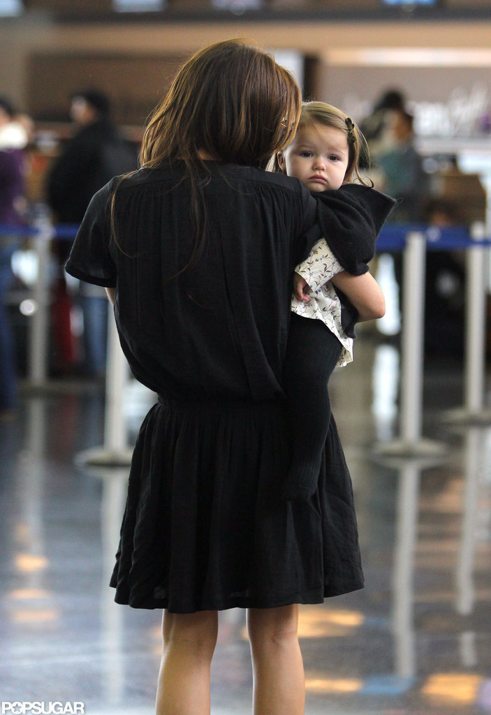 Harper Beckham peeked out over Victoria Beckham's shoulder.