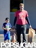 Chris Martin held bags of toys while leaving the store with Moses Martin.