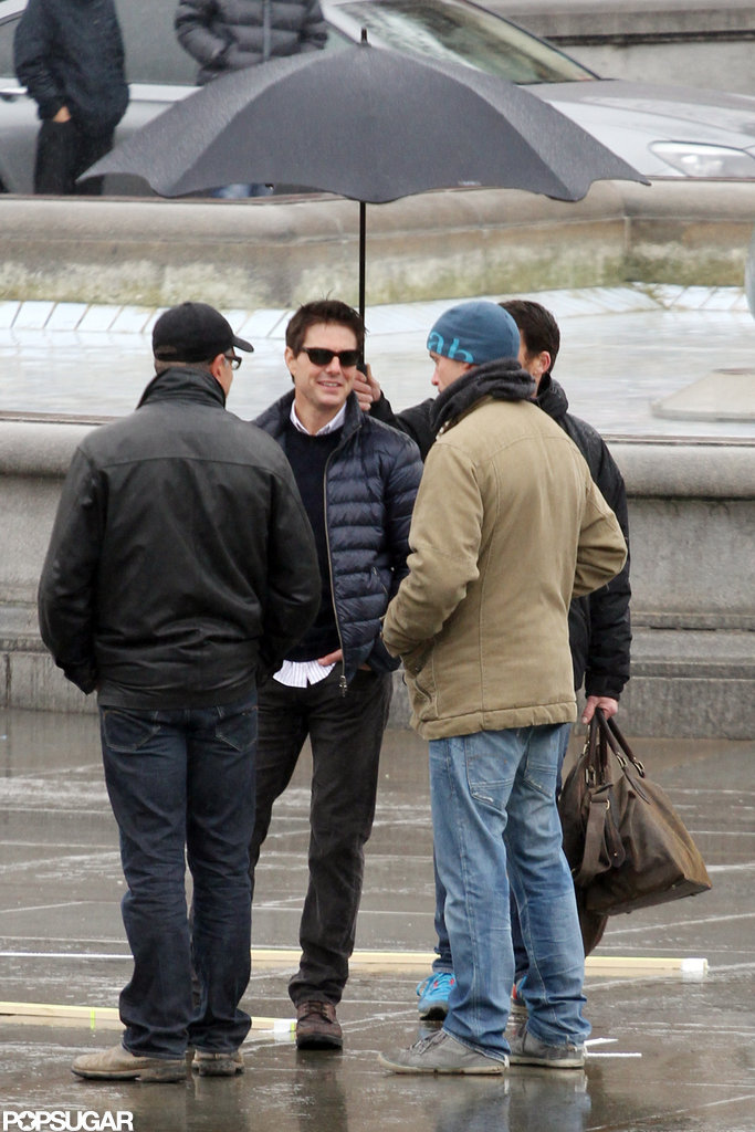 Tom Cruise stood under an umbrella in London.