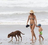 A pregnant Gisele Bündchen wore a bikini and walked on the beach in South America with Benjamin Brady in July.
