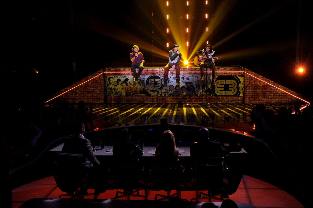 Emblem3 sat on stage during a performance.