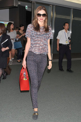 In a sheer printed top, dark leopard print pants, Céline loafers, and a bag for an always appropriate pop of red, Miranda arrived in Tokyo looking ready for the day.