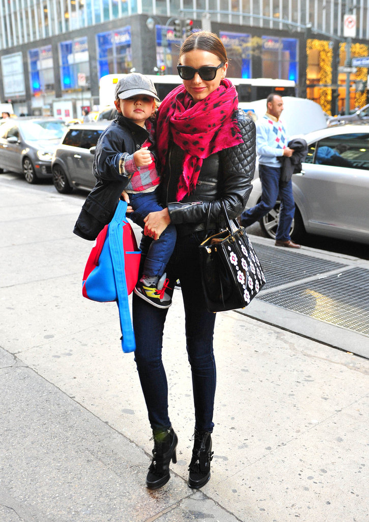 With son Flynn in hand, Miranda donned a mommy-on-the-go look with a Balenciaga quilted jacket, hot-pink pashmina, skinny jeans, Tabitha Simmons lace-up ankle boots, and a Prada bag adorned with floral appliqués.