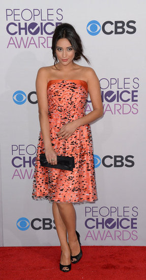 Pretty Little Liars actress Shay Mitchell showed off her penchant for color — and for prints — via this printed strapless dress. To finish the look off, she added peep-toe pumps and a long black clutch.