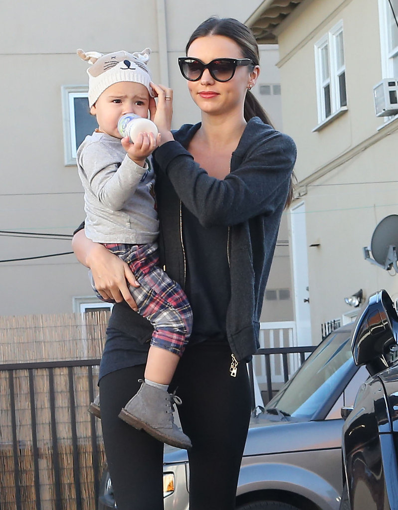 Miranda Kerr tucked Flynn Bloom's hat on.