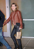 Ellen Pompeo married black and brown in a chestnut leather jacket, dark denim, black leather boots, and an embellished clutch.