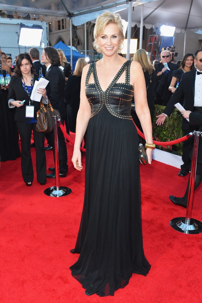 Jane Lynch went edgy in a black leather bodice with pleated skirt gown, textured clutch, and gold hoops