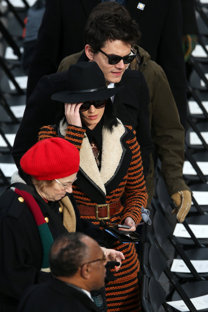 Katy Perry, along with John Mayer, stepped out at the capitol in a rust-orange-and-black-striped and belted Rodarte coat and wide-brimmed fedora.