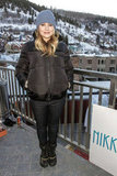 Kristen Bell bundled up in a Coach brown puffer jacket, black snow boots, and a Coach gray knit beanie.