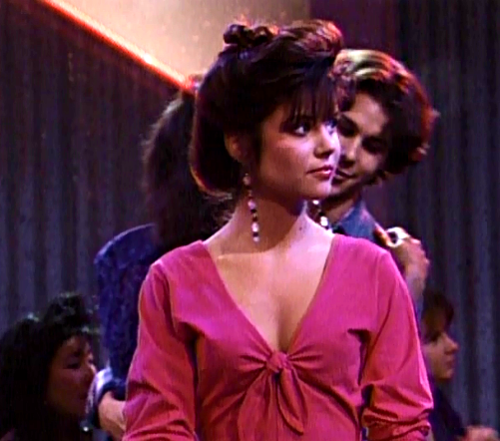 For her first time at the club (with a fake ID, obviously), Kelly tries to look as mature as possible. She opts for a fuchsia tie-front top, drop earrings, and a messy chignon. She looks beautiful, even when she spots her boss/boyfriend dancing with another girl. Source: Tumblr user savedbythebellsabrina