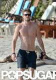 Shirtless Liam Hemsworth wore shades on the beach.