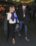 Emily Blunt's NYC arrival included an ivory sweater, black leggings, a printed scarf, Isabel Marant sneakers, and a bright cobalt bag.
