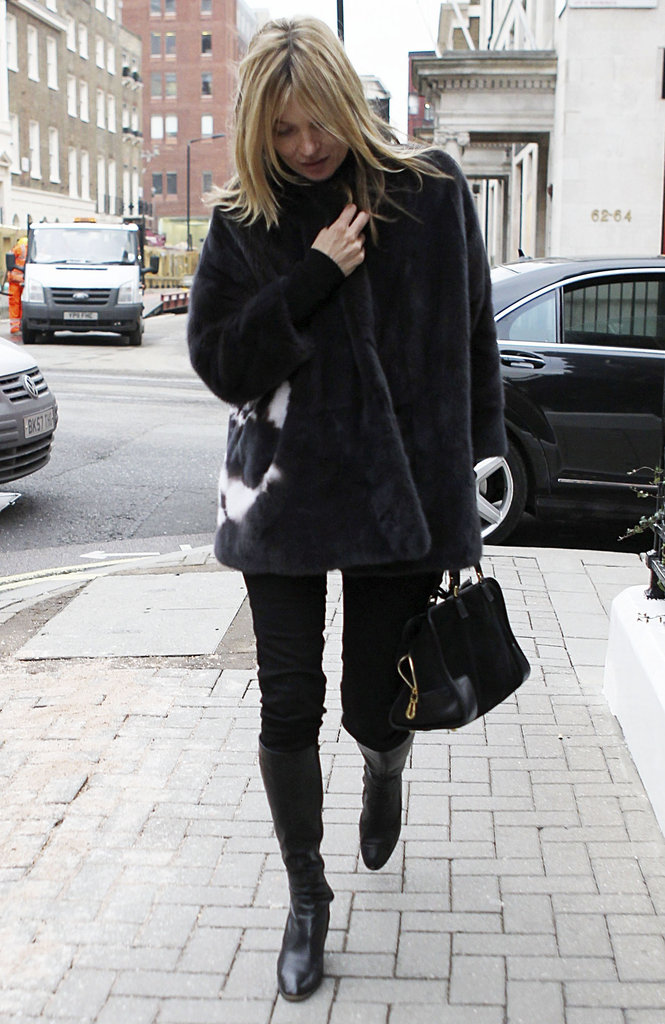 Kate Moss strolled London in a plush gray-and-white fur coat, black skinny jeans, black knee-high boots, and a black satchel.