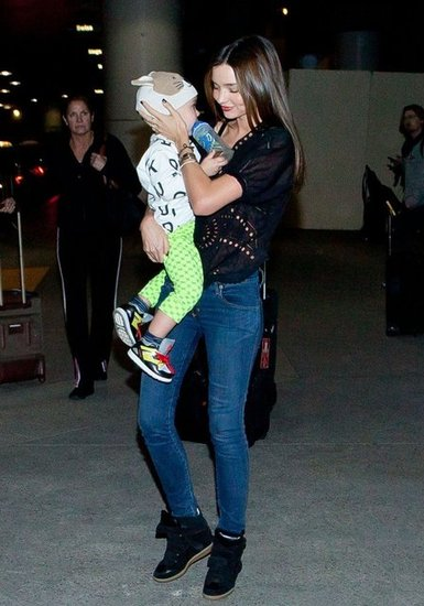 Miranda Kerr arrived at LAX airport balancing her black high-top Isabel Marant sneakers with a holey top.