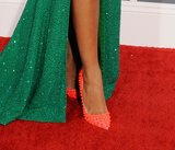 Solane Knowles offset her shimmering emerald-green gown with a pair of statement-making neon spiked pumps by Christian Louboutin.