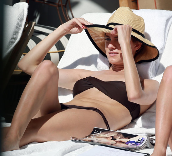 Allison Williams protected her face with a straw hat.